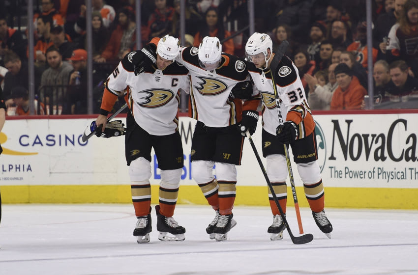 PHILADELPHIA, PA - DECEMBER 17: Anaheim Ducks Center Ryan Getzlaf (15) and Anaheim Ducks Defenceman Jacob Larsson (32) help injured teammate Anaheim Ducks Right Wing Troy Terry (61) off the ice during the game between the Anaheim Ducks and the Philadelphia Flyers on December 17, 2019, at the Wells Fargo Center in Philadelphia, PA. (Photo by Andy Lewis/Icon Sportswire via Getty Images)
