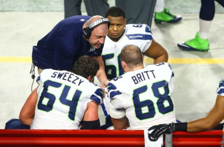 Dec 21, 2014; Glendale, AZ, USA; Seattle Seahawks offensive line coach Tom Cable (left) talks with offensive guard J.R. Sweezy (64) and offensive tackle Justin Britt (68) on the sidelines against the Arizona Cardinals at University of Phoenix Stadium. The Seahawks defeated the Cardinals 35-6. Mandatory Credit: Mark J. Rebilas-USA TODAY Sports