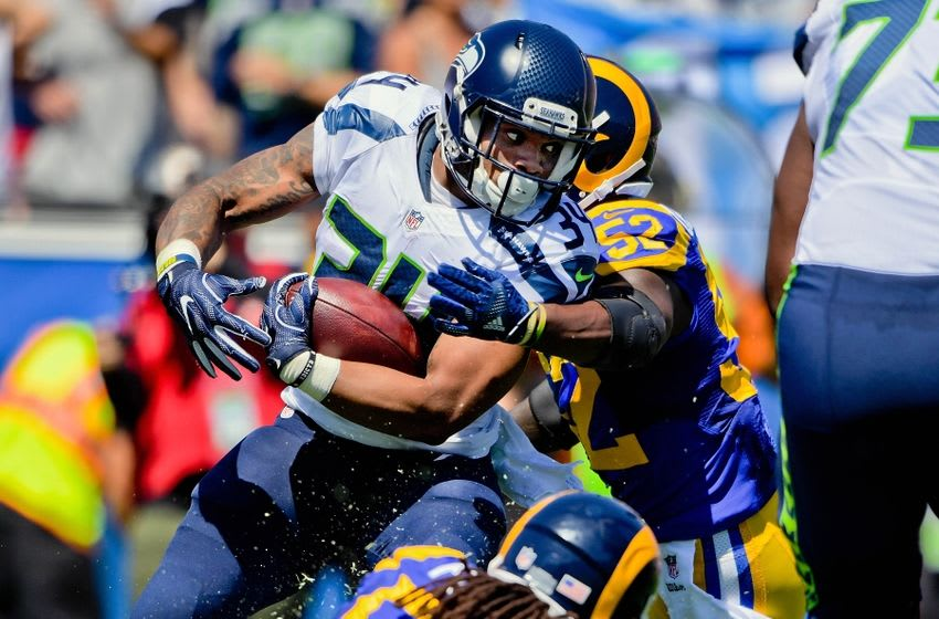 Sep 18, 2016; Los Angeles, CA, USA; Seattle Seahawks running back Thomas Rawls (34) rushes against Los Angeles Rams outside linebacker Alec Ogletree (52) during the second half of a NFL game at Los Angeles Memorial Coliseum. Mandatory Credit: Kirby Lee-USA TODAY Sports