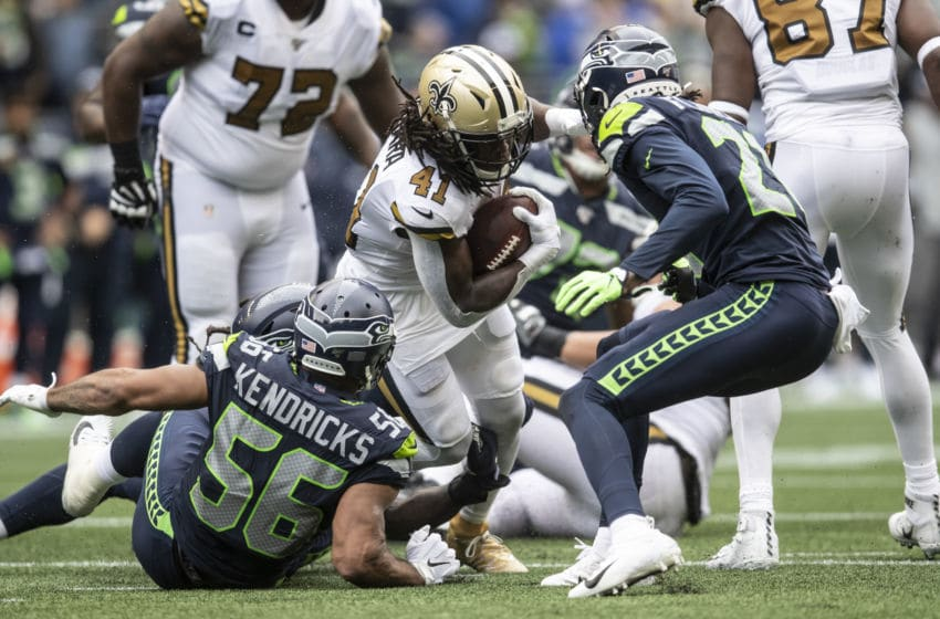 SEATTLE, WA - SEPTEMBER 22: Running back Alvin Kamara #41 of the New Orleans Saints rushes teh ball as linebacker Mychal Kendricks #56 of the Seattle Seahawks and defensive back Tre Flowers #21 during the second half of a game at CenturyLInk Field on September 22, 2019 in Seattle, Washington. The Saints won 33-27. (Photo by Stephen Brashear/Getty Images)