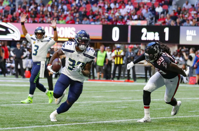 ATLANTA, GA - OCTOBER 27: Chris Carson #32 of the Seattle Seahawks breaks away from De'Vondre Campbell #59 of the Atlanta Falcons to score a touchdown as Russell Wilson #3 reacts in the background in the first half of an NFL game at Mercedes-Benz Stadium on October 27, 2019 in Atlanta, Georgia. (Photo by Todd Kirkland/Getty Images)