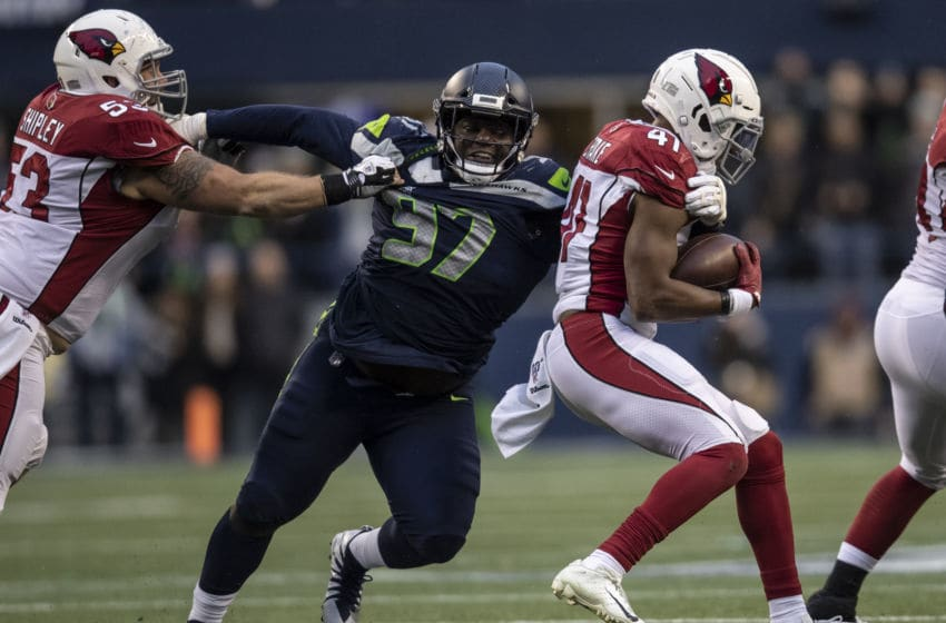 SEATTLE, WA - DECEMBER 22: Defensive lineman Poona Ford #97 of the Seattle Seahawks tackles running back Kenyan Drake #41 of the Arizona Cardinals in the the back field during game at CenturyLink Field on December 22, 2019 in Seattle, Washington. The Cardinals won 27-13. (Photo by Stephen Brashear/Getty Images)
