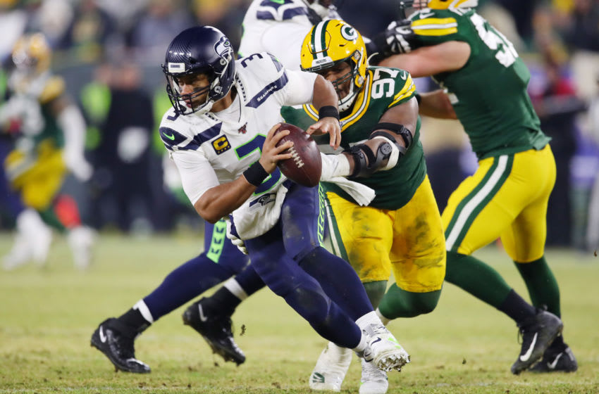 GREEN BAY, WISCONSIN - JANUARY 12: Kenny Clark #97 of the Green Bay Packers attempts to tackle Russell Wilson #3 of the Seattle Seahawks during the first half in the NFC Divisional Playoff game at Lambeau Field on January 12, 2020 in Green Bay, Wisconsin. (Photo by Gregory Shamus/Getty Images)