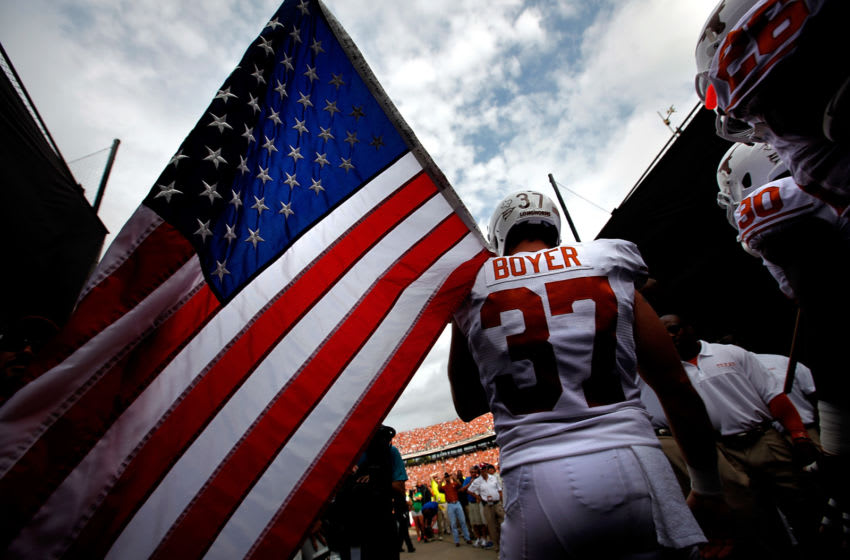 DALLAS, TX - OCTOBER 13: Nate Boyer #37 of the Texas Longhorns carries an American flag as the Texas Longhorns take to the field against the Oklahoma Sooners at Cotton Bowl on October 13, 2012 in Dallas, Texas. (Photo by Tom Pennington/Getty Images)