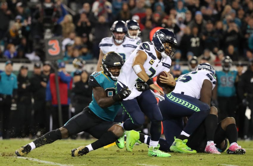 JACKSONVILLE, FL - DECEMBER 10: Russell Wilson #3 of the Seattle Seahawks is tackled by Yannick Ngakoue #91 of the Jacksonville Jaguars during the second half of their game at EverBank Field on December 10, 2017 in Jacksonville, Florida. (Photo by Logan Bowles/Getty Images)