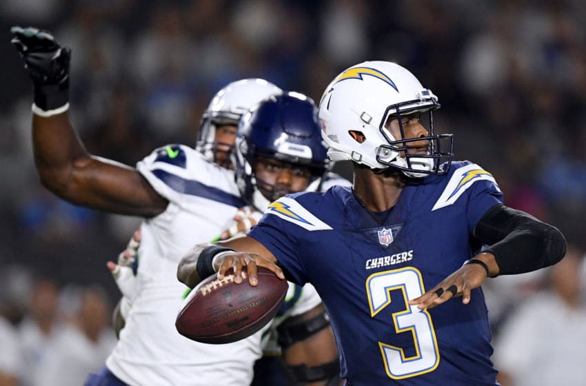CARSON, CA - AUGUST 18: Geno Smith #3 of the Los Angeles Chargers passes in the pocket in front of Rasheem Green #94 of the Seattle Seahawks during the second quarter of a presseason game at StubHub Center on August 18, 2018 in Carson, California. (Photo by Harry How/Getty Images)