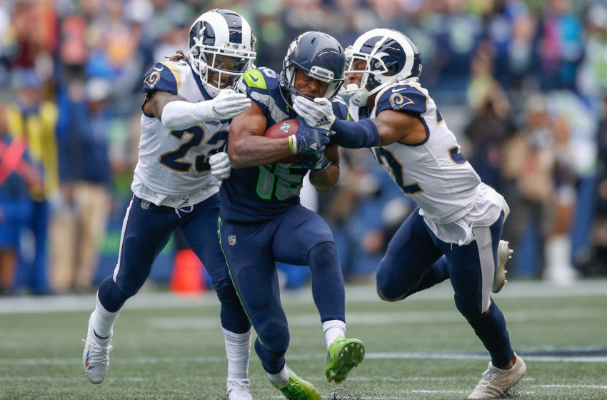 SEATTLE, WA - OCTOBER 07: Wide receiver Tyler Lockett #16 of the Seattle Seahawks is tackled by cornerback Nickell Robey-Coleman #23 and cornerback Troy Hill #32 of the Los Angeles Rams on a 44 yard catch in the fourth quarter at CenturyLink Field on October 7, 2018 in Seattle, Washington. The Rams beat the Seahawks 33-31. (Photo by Otto Greule Jr/Getty Images)