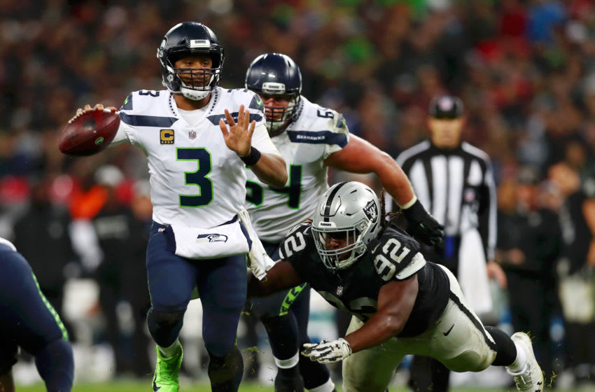 LONDON, ENGLAND - OCTOBER 14: Russell Wilson of Seattle Seahawks is tackled by P.J. Hall of Oakland Raiders during the NFL International series match between Seattle Seahawks and Oakland Raiders at Wembley Stadium on October 14, 2018 in London, England. (Photo by Naomi Baker/Getty Images)