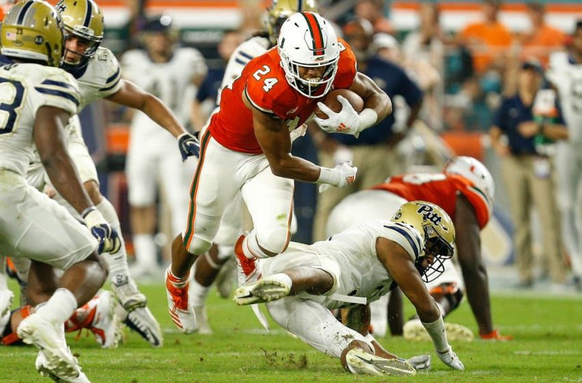 MIAMI GARDENS, FL - NOVEMBER 24: Travis Homer #24 of the Miami Hurricanes breaks a tackle against the Pittsburgh Panthers during the second half at Hard Rock Stadium on November 24, 2018 in Miami Gardens, Florida. (Photo by Michael Reaves/Getty Images)