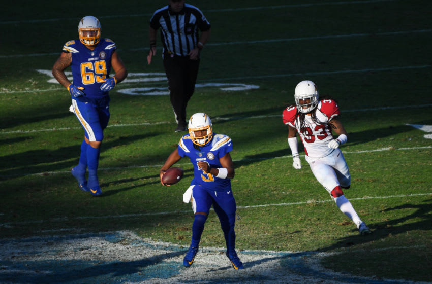 CARSON, CA - NOVEMBER 25: Quarterback Geno Smith #3 of the Los Angeles Chargers runs ahead of defensive back Tre Boston #33 of the Arizona Cardinals and offensive tackle Sam Tevi #69 in the fourth quarter at StubHub Center on November 25, 2018 in Carson, California. (Photo by Harry How/Getty Images)