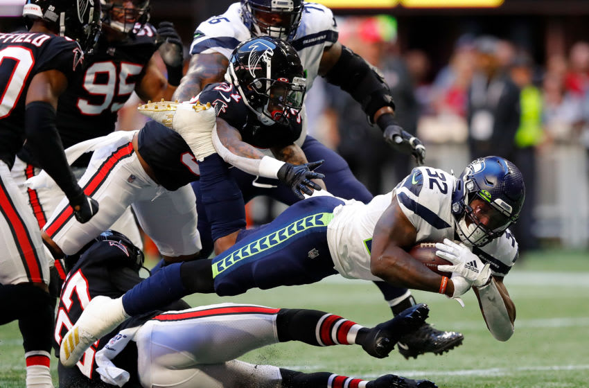 ATLANTA, GEORGIA - OCTOBER 27: Chris Carson #32 of the Seattle Seahawks dives for more yardage as he is tackled by Damontae Kazee #27 and Ricardo Allen #37 of the Atlanta Falcons at Mercedes-Benz Stadium on October 27, 2019 in Atlanta, Georgia. (Photo by Kevin C. Cox/Getty Images)
