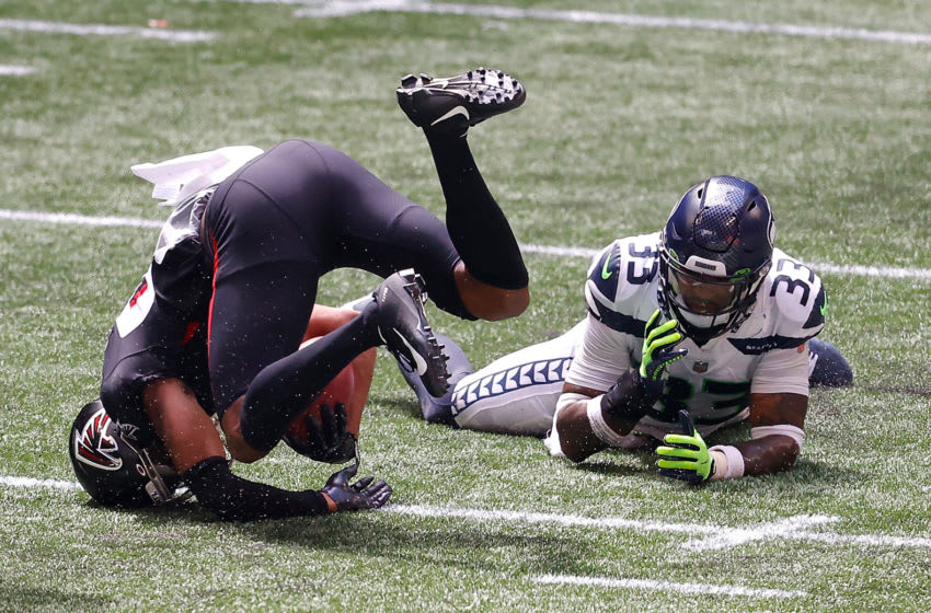 ATLANTA, GEORGIA - SEPTEMBER 13: Jamal Adams #33 of the Seattle Seahawks tackles Russell Gage #83 of the Atlanta Falcons after a reception in the first half at Mercedes-Benz Stadium on September 13, 2020 in Atlanta, Georgia. (Photo by Kevin C. Cox/Getty Images)