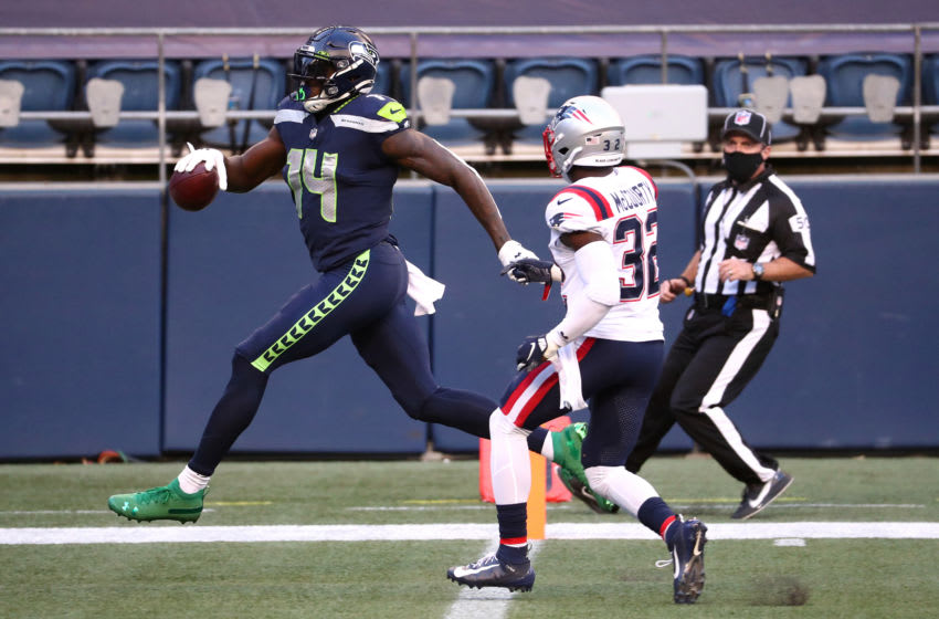 SEATTLE, WASHINGTON - SEPTEMBER 20: DK Metcalf #14 of the Seattle Seahawks scores a second quarter touchdown against Devin McCourty #32 of the New England Patriots at CenturyLink Field on September 20, 2020 in Seattle, Washington. (Photo by Abbie Parr/Getty Images)