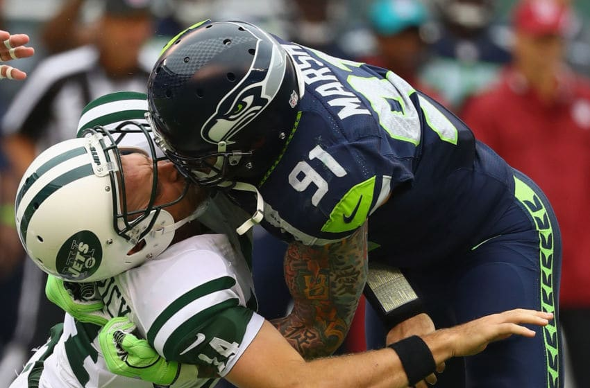 EAST RUTHERFORD, NJ - OCTOBER 02: Cassius Marsh #91 of the Seattle Seahawks hits his helmet against quarterback Ryan Fitzpatrick #14 of the New York Jets for a penalty 'Roughing the Passer' in the second quarter at MetLife Stadium on October 2, 2016 in East Rutherford, New Jersey. (Photo by Al Bello/Getty Images)