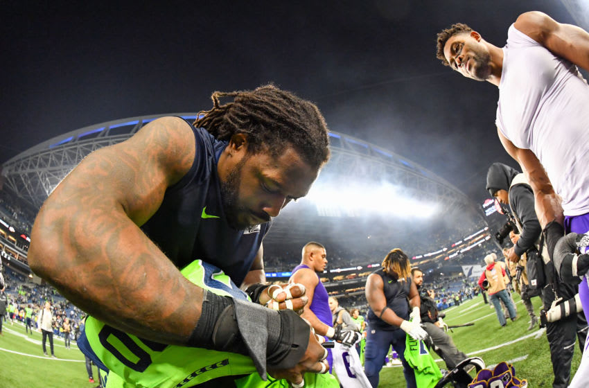 SEATTLE, WASHINGTON - DECEMBER 02: Jadeveon Clowney #90 of the Seattle Seahawks, left, signs his jersey to exchange with Danielle Hunter #99 of the Minnesota Vikings after the game at CenturyLink Field on December 02, 2019 in Seattle, Washington. The Seattle Seahawks won, 37-30. (Photo by Alika Jenner/Getty Images)