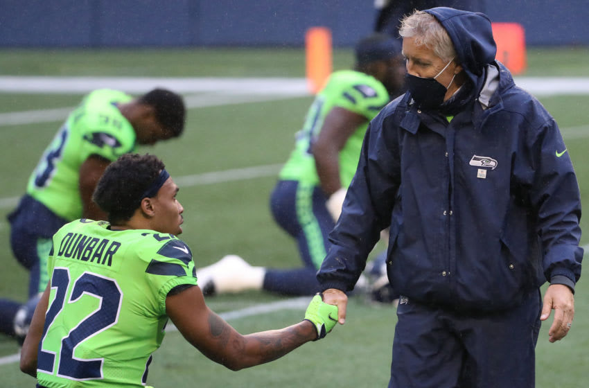 SEATTLE, WASHINGTON - OCTOBER 11: Quinton Dunbar #22 and head coach Pete Carroll of the Seattle Seahawks shake hands before their game against the Minnesota Vikings at CenturyLink Field on October 11, 2020 in Seattle, Washington. (Photo by Abbie Parr/Getty Images)