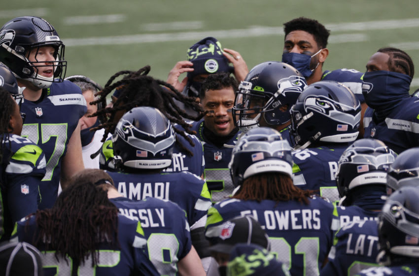 SEATTLE, WASHINGTON - JANUARY 09: Quarterback Russell Wilson #3 of the Seattle Seahawks and team huddle on the field prior to the NFC Wild Card Playoff game against the Los Angeles Rams at Lumen Field on January 09, 2021 in Seattle, Washington. (Photo by Steph Chambers/Getty Images)