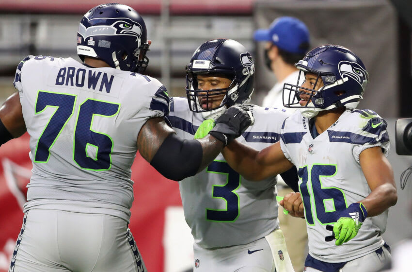 GLENDALE, ARIZONA - OCTOBER 25: Wide receiver Tyler Lockett #16 of the Seattle Seahawks is congratulated by offensive tackle Duane Brown #76 and quarterback Russell Wilson #3 after Lockett scored a receiving touchdown against the Arizona Cardinals in the first quarter of the game at State Farm Stadium on October 25, 2020 in Glendale, Arizona. (Photo by Christian Petersen/Getty Images)