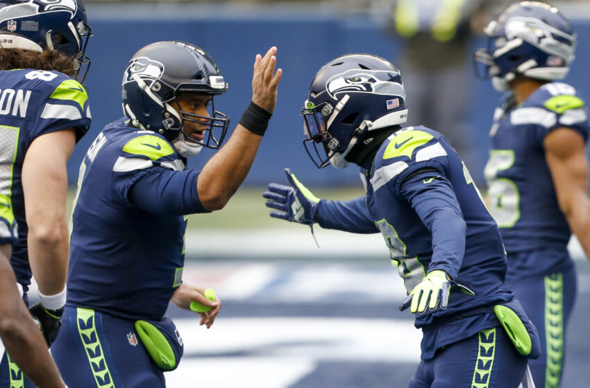 Dec 13, 2020; Seattle, Washington, USA; Seattle Seahawks quarterback Russell Wilson (3) celebrates with wide receiver Freddie Swain (18) after throwing a touchdown pass to Swain against the New York Jets during the first quarter at Lumen Field. Mandatory Credit: Joe Nicholson-USA TODAY Sports