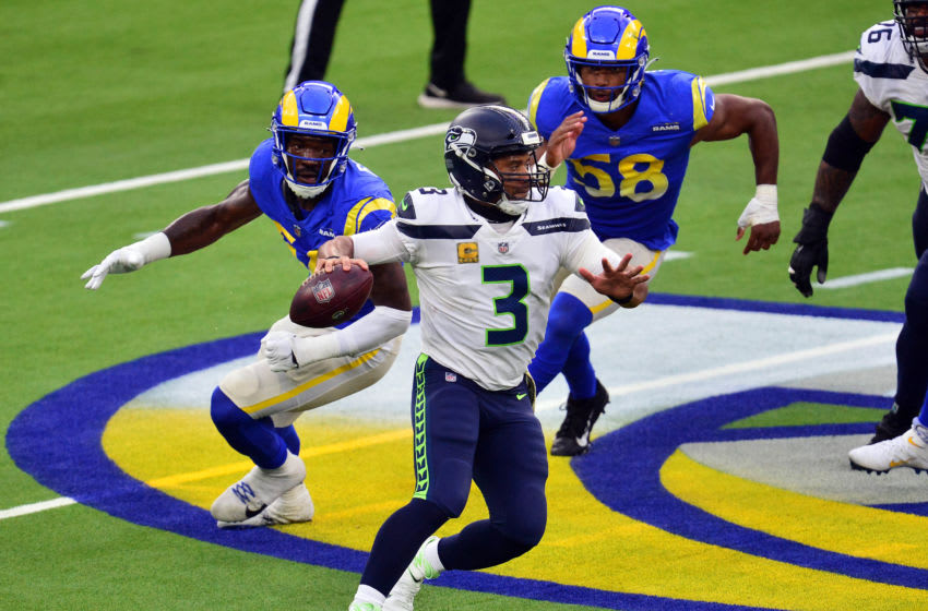 Nov 15, 2020; Inglewood, California, USA; Seattle Seahawks quarterback Russell Wilson (3) throws as Los Angeles Rams linebacker Justin Hollins (58) and linebacker Troy Reeder (51) move in during the first half at SoFi Stadium. Mandatory Credit: Gary A. Vasquez-USA TODAY Sports
