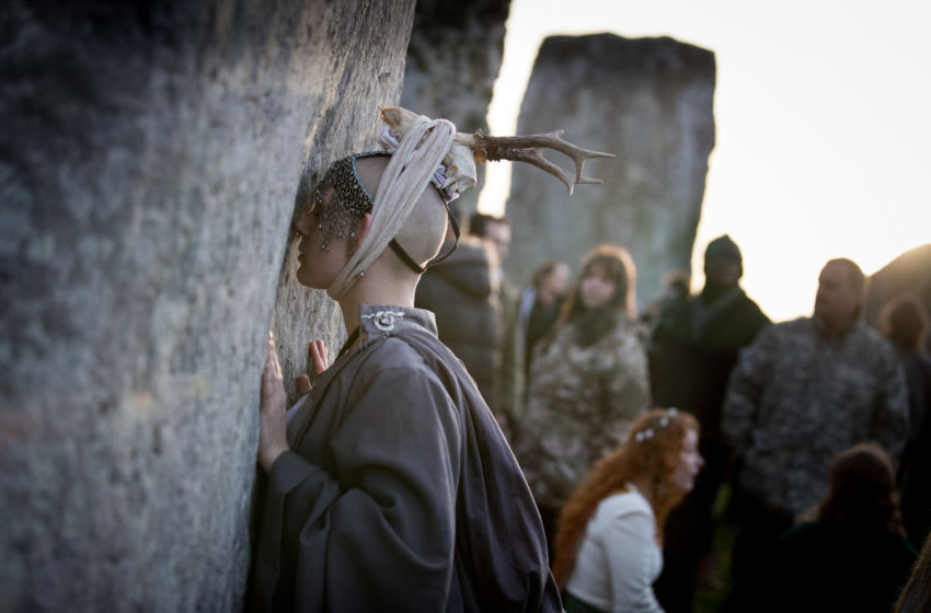 AMESBURY, ENGLAND - DECEMBER 22: A woman holds one of the stones as druids, pagans and revellers gather at Stonehenge, hoping to see the sun rise, as they take part in a winter solstice ceremony at the ancient neolithic monument of Stonehenge near Amesbury on December 22, 2018 in Wiltshire, England. A large crowd gathered at the famous historic stone circle, a UNESCO listed ancient monument to celebrate the sunrise closest to the Winter Solstice, the shortest day of the year. The event is claimed to be more important in the pagan calendar than the summer solstice, because it marks the 're-birth' of the Sun for the New Year. (Photo by Matt Cardy/Getty Images)