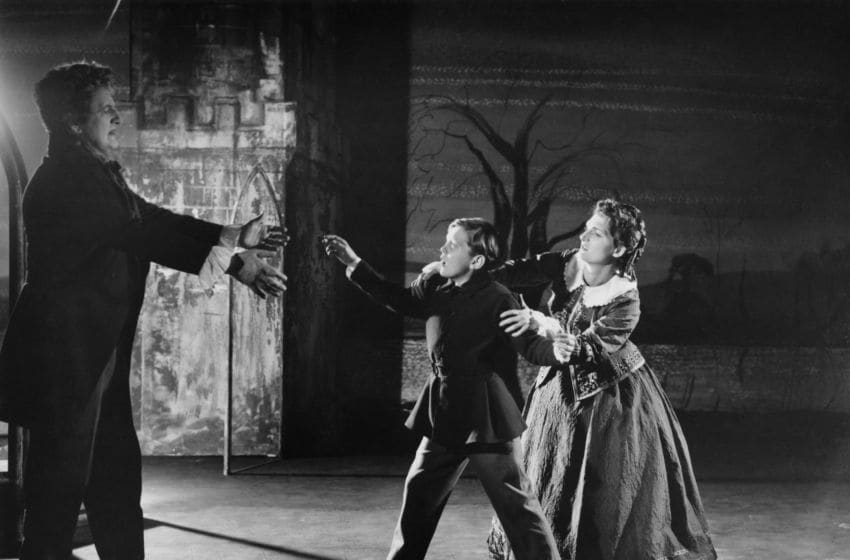 From left to right, Tenor Peter Pears (1910 - 1986) as Quint, child soprano David Hemmings (1941 - 2003) as Miles, and Jennifer Vyvyan (1925 - 1974) as the Governess in the English Opera Group's production of Benjamin Britten's 'The Turn Of The Screw', at Sadler's Wells Theatre, London, 13th October 1954. (Photo by Denis De Marney/Hulton Archive/Getty Images)
