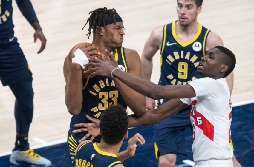 Jan 25, 2021; Indianapolis, Indiana, USA; Indiana Pacers center Myles Turner (33) rebounds the ball over Toronto Raptors forward Chris Boucher (25) in the fourth quarter at Bankers Life Fieldhouse. Mandatory Credit: Trevor Ruszkowski-USA TODAY Sports