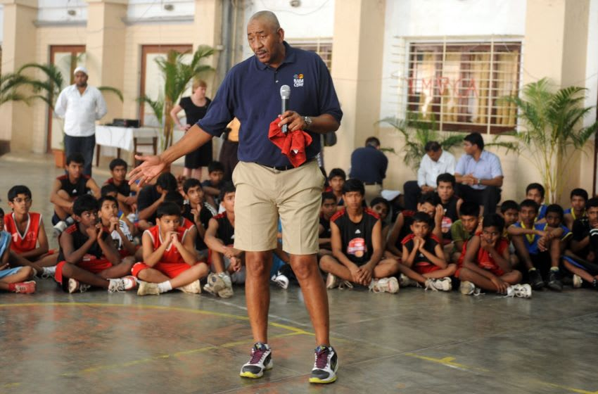 """Legendary NBA Hall of Famer George """"The Iceman"""" Gervin of the US gives basketball shooting tips to Indian schoolchildren during a coaching clinic in Mumbai on February 24, 2011. Two-time WNBA champion Katie Smith joined Gervin at the session, organised by the U.S. Department of State's SportsUnited Sports Envoy Program, which aims to develop grassroots sports overseas. AFP PHOTO/ Punit PARANJPE (Photo credit should read PUNIT PARANJPE/AFP via Getty Images)"""