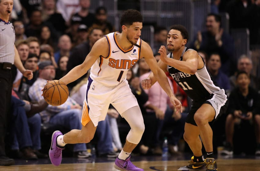 PHOENIX, ARIZONA - JANUARY 20: Devin Booker #1 of the Phoenix Suns handles the ball against Bryn Forbes #11 of the San Antonio Spurs during the NBA game at Talking Stick Resort Arena on January 20, 2020 in Phoenix, Arizona. The Spurs defeated the Suns 120-118. NOTE TO USER: User expressly acknowledges and agrees that, by downloading and or using this photograph, user is consenting to the terms and conditions of the Getty Images License Agreement. (Photo by Christian Petersen/Getty Images)