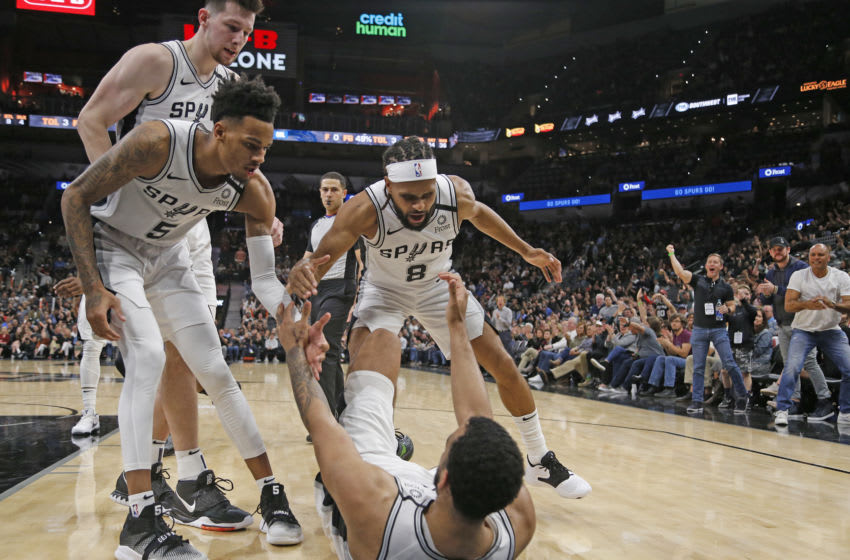SAN ANTONIO, TX - FEBRUARY 29: Patty Mills #8 of the San Antonio Spurs and Dejounte Murray #5 help Trey Lyles #41 up after a one and during second half action (Photo by Ronald Cortes/Getty Images)