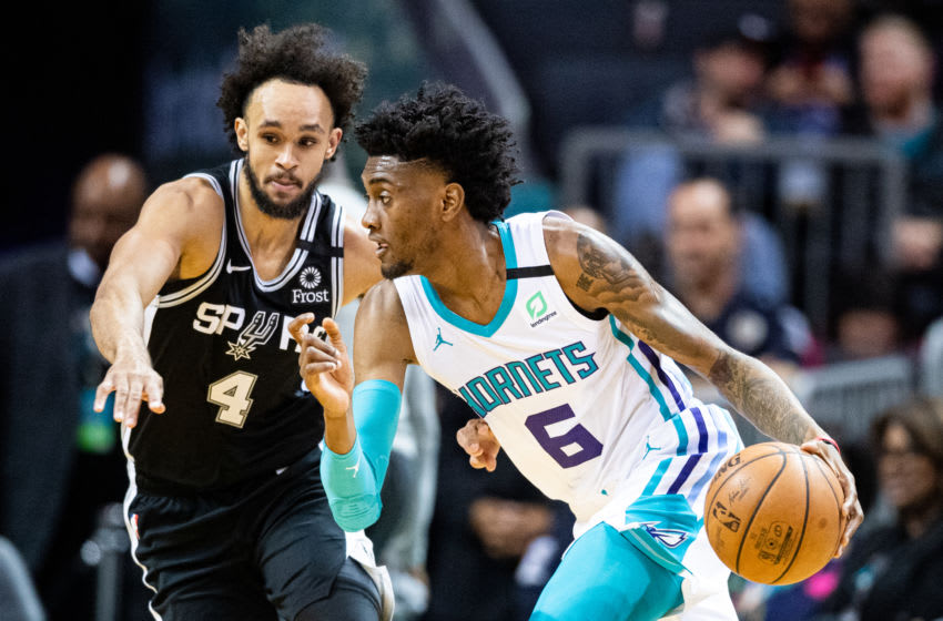 CHARLOTTE, NORTH CAROLINA - MARCH 03: Jalen McDaniels #6 of the Charlotte Hornets is guarded by Derrick White #4 of the San Antonio Spurs during the first quarter of their game at Spectrum Center (Photo by Jacob Kupferman/Getty Images)