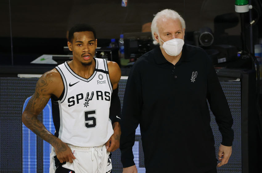LAKE BUENA VISTA, FLORIDA - AUGUST 13: Gregg Popovich of the San Antonio Spurs talks with Dejounte Murray #5 of the San Antonio Spurs during the first quarter against the Utah Jazz at The Field House at ESPN Wide World Of Sports Complex on August 13, 2020 in Lake Buena Vista, Florida. NOTE TO USER: User expressly acknowledges and agrees that, by downloading and or using this photograph, User is consenting to the terms and conditions of the Getty Images License Agreement. (Photo by Kevin C. Cox/Getty Images)