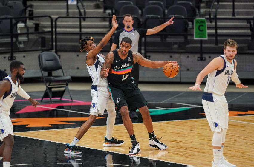 Jan 22, 2021; San Antonio, Texas, USA; San Antonio Spurs center LaMarcus Aldridge (12) backs up against Dallas Mavericks forward Wes Iwundu (25) at the AT&T Center. Mandatory Credit: Daniel Dunn-USA TODAY Sports