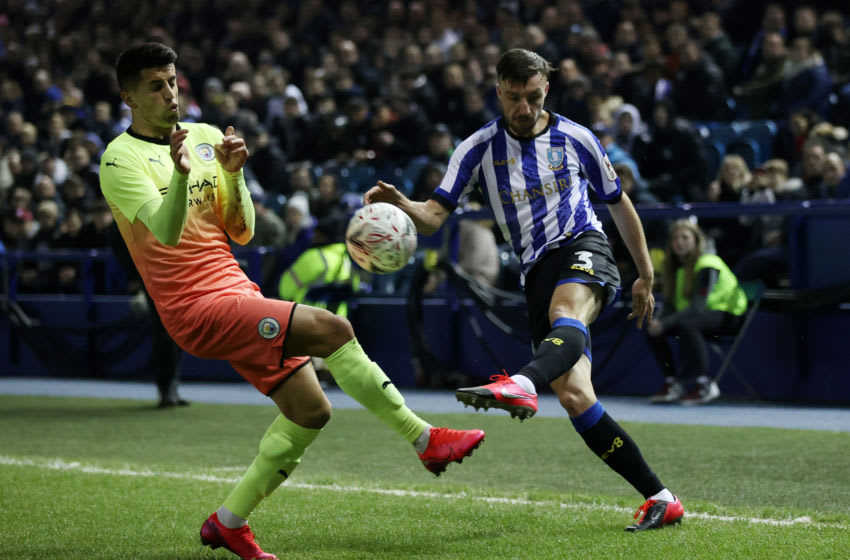 SHEFFIELD, ENGLAND - MARCH 04: Morgan Fox of Sheffield Wednesday crosses the ball with Joao Cancelo of Manchester City attempting to block during the FA Cup Fifth Round match between Sheffield Wednesday and Manchester City at Hillsborough on March 04, 2020 in Sheffield, England. (Photo by Clive Brunskill/Getty Images)