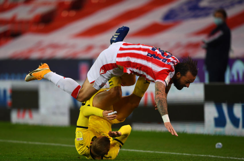 STOKE ON TRENT, ENGLAND - OCTOBER 21: Steven Fletcher of Stoke City is challenged by Michal Helik of Barnsley during the Sky Bet Championship match between Stoke City and Barnsley at Bet365 Stadium on October 21, 2020 in Stoke on Trent, England. Sporting stadiums around the UK remain under strict restrictions due to the Coronavirus Pandemic as Government social distancing laws prohibit fans inside venues resulting in games being played behind closed doors. (Photo by Gareth Copley/Getty Images)