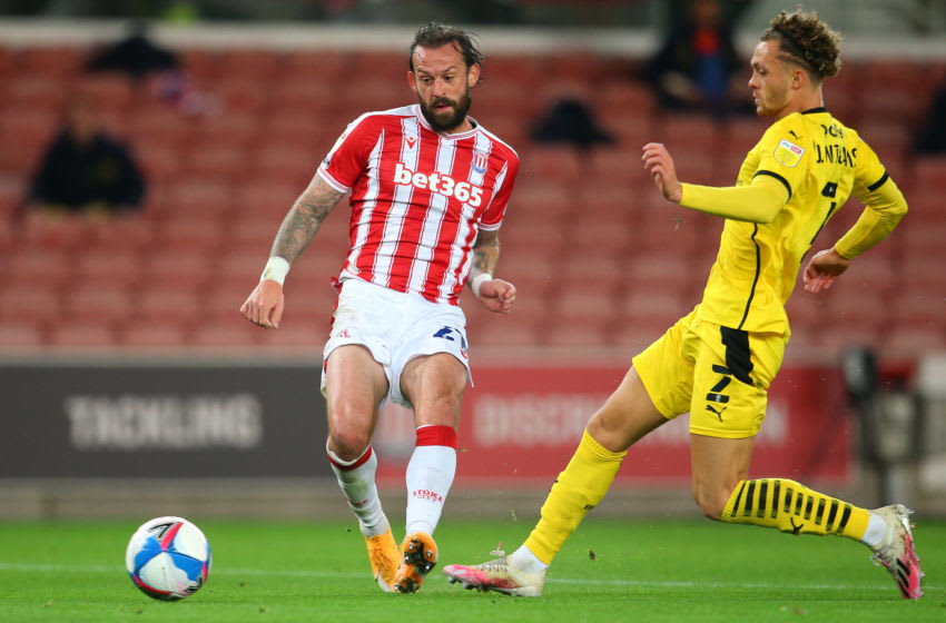 STOKE ON TRENT, ENGLAND - OCTOBER 21: Steven Fletcher of Stoke City shoots under pressure from Jordan Williams of Barnsley during the Sky Bet Championship match between Stoke City and Barnsley at Bet365 Stadium on October 21, 2020 in Stoke on Trent, England. Sporting stadiums around the UK remain under strict restrictions due to the Coronavirus Pandemic as Government social distancing laws prohibit fans inside venues resulting in games being played behind closed doors. (Photo by James Gill - Danehouse/Getty Images)