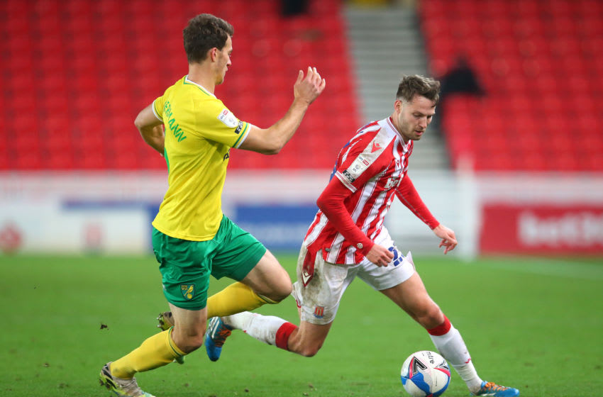 STOKE ON TRENT, ENGLAND - NOVEMBER 24: Nick Powell of Stoke City is tackled by Christoph Zimmermann of Norwich City during the Sky Bet Championship match between Stoke City and Norwich City at Bet365 Stadium on November 24, 2020 in Stoke on Trent, England. Sporting stadiums around the UK remain under strict restrictions due to the Coronavirus Pandemic as Government social distancing laws prohibit fans inside venues resulting in games being played behind closed doors. (Photo by James Gill - Danehouse/Getty Images)