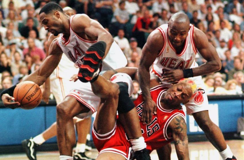 Dennis Rodman of the Chicago Bulls(C) falls to the ground with Alonzo Mourning (L) and Tim Hardaway (R) of the Miami Heat after struggling to reach a rebound (RHONA WISE/AFP via Getty Images)