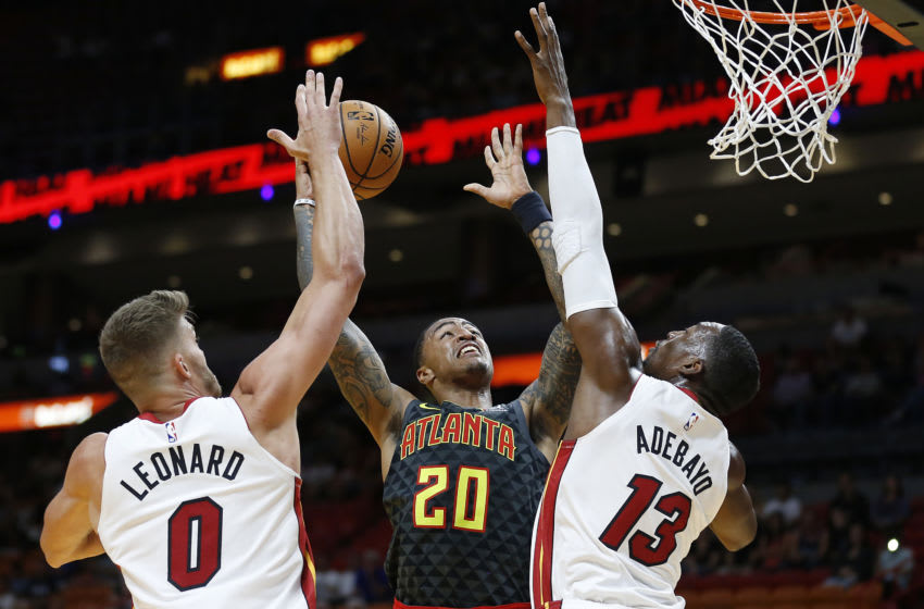 John Collins #20 of the Atlanta Hawks shoots over Bam Adebayo #13 and Meyers Leonard #0 of the Miami Heat during the first half. (Photo by Michael Reaves/Getty Images)