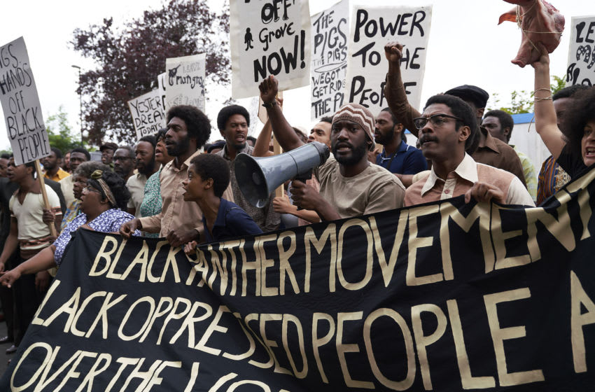 Small Axe. Pictured: Letitia Wright as Altheia Jones-LeCointe (center, dark blue shirt) and Malachi Kirby as Darcus Howe (center, holding megaphone) in