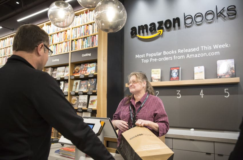SEATTLE, WA - NOVEMBER 4: Amazon associate Katherine Sotol, left, bags up a purchase for customer Don Taufen of Seattle. Washington at the newly-opened Amazon Books store on November 4, 2015 in Seattle. The online retailer opened its first brick-and-mortar book store on November 3, 2015. (Photo by Stephen Brashear/Getty Images)