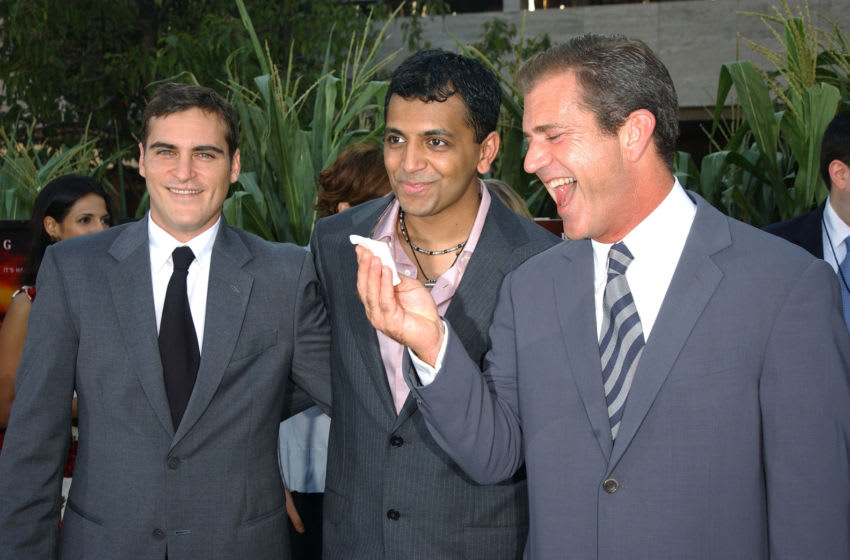 NEW YORK - JULY 29: Writer/Director M. Night Shyamalan (C) poses with actors Mel Gibson (R) and Joaquin Phoenix at the world premiere of