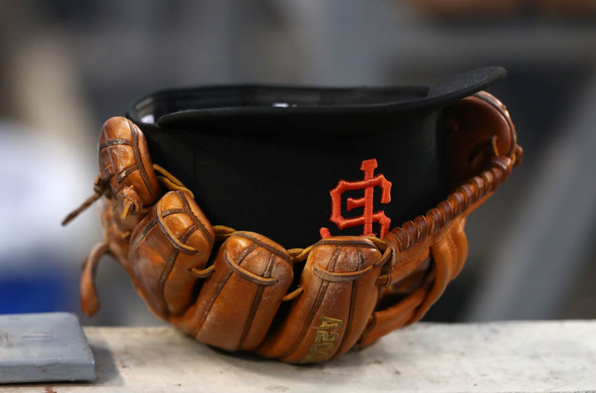 A SF Giants player' hat in a catching glove is seen in the dugout. (Photo by Victor Decolongon/Getty Images)