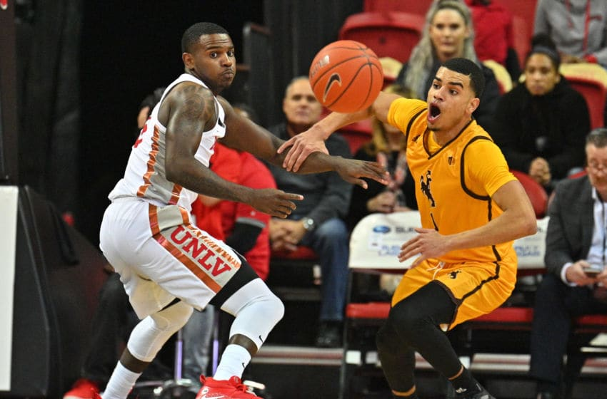LAS VEGAS, NEVADA - JANUARY 05: Amauri Hardy #3 of the UNLV Rebels and Justin James #1 of the Wyoming Cowboys chase after a loose ball during their game at the Thomas & Mack Center on January 05, 2019 in Las Vegas, Nevada. (Photo by Sam Wasson/Getty Images)