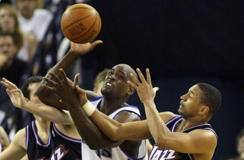 Sacramento Kings' forward Chris Webber (C) tries to recover a rebound while getting fouled by Utah Jazz's guard Mark Jackson (R) as Jazz's forward Scott Padgett looks on during the fourth quarter of the first round of the Western Conference playoffs, 19 April 2003, at ARCO Arena in Sacramento, California. The Kings defeated the Jazz 96-90. AFP PHOTO/John G. MABANGLO (Photo by JOHN G. MABANGLO / AFP) (Photo credit should read JOHN G. MABANGLO/AFP via Getty Images)