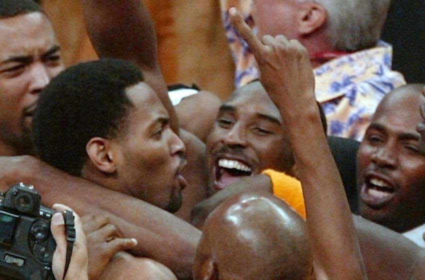 LOS ANGELES, UNITED STATES: Robert Horry (L) of the Los Angeles Lakers is mobbed by teammates including Kobe Bryant (R) after he made the winning three-point basket to give the Lakers a 100-99 victory over the Sacramento Kings during Game 4 of the Western Conference Finals at the Staples Center in Los Angeles 26 May, 2002. The Lakers tied the best-of-seven series 2-2. AFP PHOTO/Robert SULLIVAN (Photo credit should read ROBERT SULLIVAN/AFP via Getty Images)