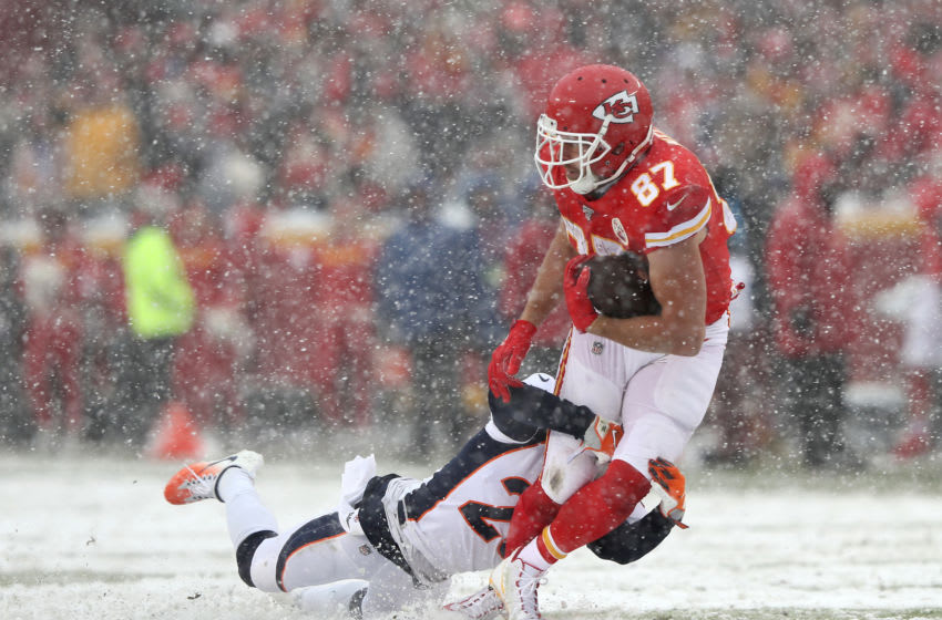 KANSAS CITY, MISSOURI - DECEMBER 15: Tight end Travis Kelce #87 of the Kansas City Chiefs makes a catch as cornerback Chris Harris #25 of the Denver Broncos makes the tackle during the game at Arrowhead Stadium on December 15, 2019 in Kansas City, Missouri. (Photo by Jamie Squire/Getty Images)