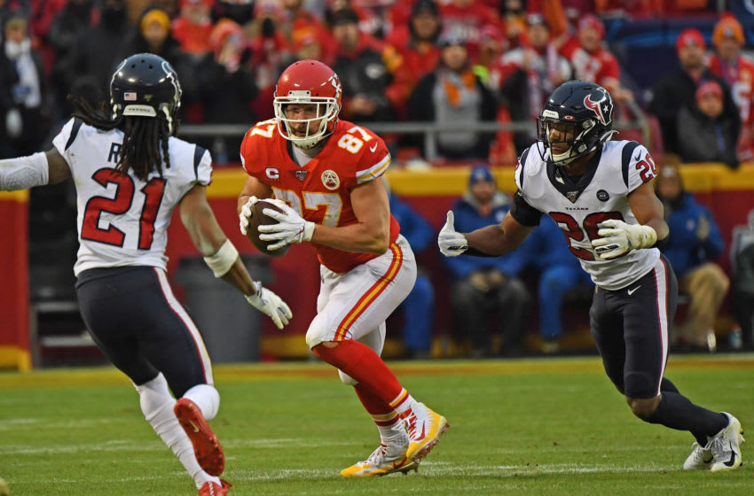 KANSAS CITY, MISSOURI - JANUARY 12: Tight end Travis Kelce #87 of the Kansas City Chiefs runs up field between strong safety Justin Reid #20 and cornerback Bradley Roby #21 of the Houston Texans in the second half during the AFC Divisional playoff game at Arrowhead Stadium on January 12, 2020 in Kansas City, Missouri. (Photo by Peter G. Aiken/Getty Images)
