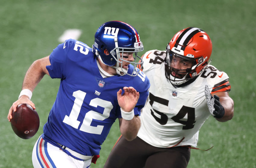 EAST RUTHERFORD, NEW JERSEY - DECEMBER 20: Colt McCoy #12 of the New York Giants scrambles ahead of Olivier Vernon #54 of the Cleveland Browns during the second quarter of a game at MetLife Stadium on December 20, 2020 in East Rutherford, New Jersey. (Photo by Al Bello/Getty Images)