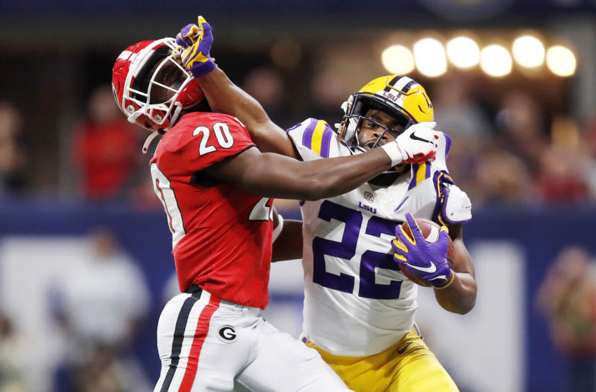 ATLANTA, GEORGIA - DECEMBER 07: Clyde Edwards-Helaire #22 of the LSU Tigers stiff arms J.R. Reed #20 of the Georgia Bulldogs in the second half during the SEC Championship game at Mercedes-Benz Stadium on December 07, 2019 in Atlanta, Georgia. (Photo by Todd Kirkland/Getty Images)